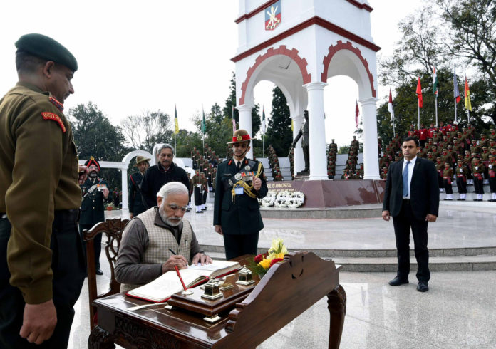 The Prime Minister, Shri Narendra Modi signing visitors' book at the War Memorial in Indian Military Academy, Dehradun, ahead of the Combined Commanders Conference, on January 21, 2017. The Union Minister for Defence, Shri Manohar Parrikar is also seen.
