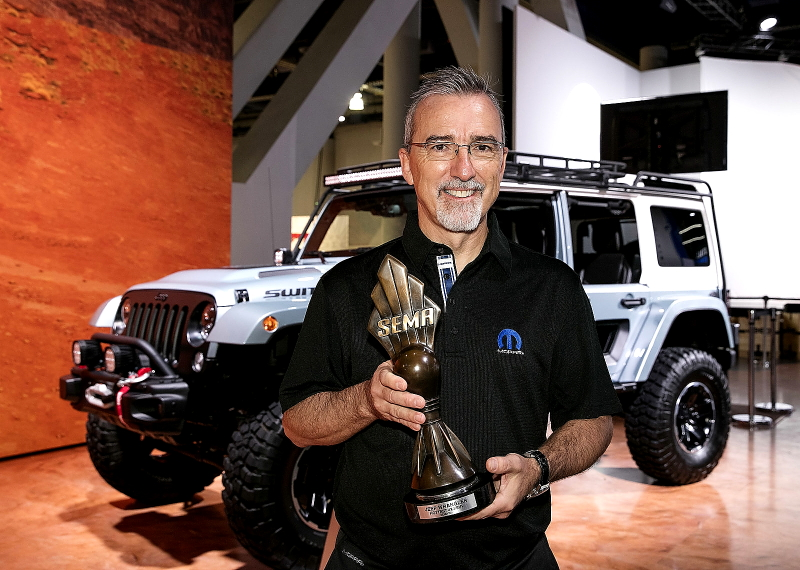"""Pietro Gorlier, Head of Parts and Service (Mopar) - FCA, with the """"Hottest 4x4-SUV"""" award, claimed by the Jeep(r) Wrangler for the eighth consecutive year at the Specialty Equipment Market Association (SEMA) Show in Las Vegas. (PRNewsfoto/FCA US LLC)"""