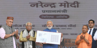 The Prime Minister, Shri Narendra Modi at the unveiling ceremony of the several projects in Varanasi, Uttar Pradesh on February 19, 2019. The Governor of Uttar Pradesh, Shri Ram Naik, the Chief Minister of Uttar Pradesh, Yogi Adityanath and the Minister of State for Communications (I/C) and Railways, Shri Manoj Sinha are also seen.
