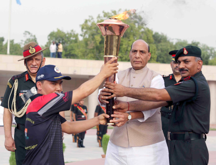 The Union Minister for Defence, Shri Rajnath Singh handing over the Victory Flame (mashal) of Kargil War to the first torch bearer army shooter Subedar Jitu Rai to be carried by Indian Army's outstanding sportsmen and war heroes to Kargil War Memorial, at Dras, in New Delhi on July 14, 2019. The Chief of Army Staff, General Bipin Rawat is also seen.