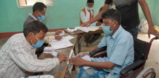 Polling official administering indelible ink to a divyang voter, at a polling booth, during the first phase of the Assam Assembly Election, at Dhekiajuli, in Sonitpur district, Assam on March 27, 2021