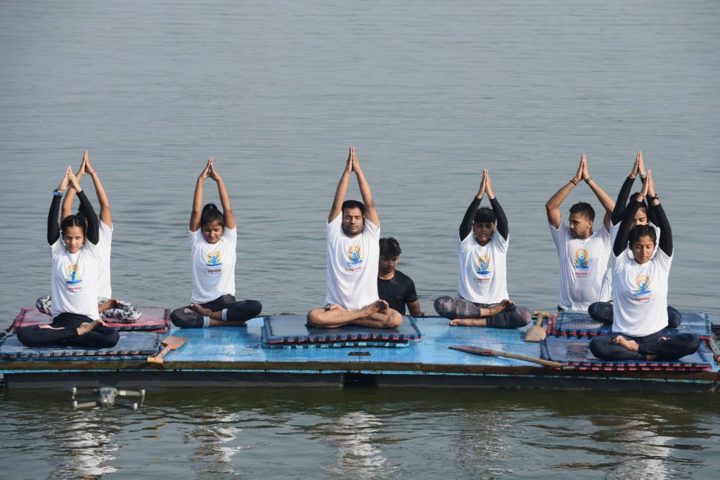 Students of a Water Club perform Yoga, on the occasion of the 7th International Day of Yoga 2021, at Yamuna River, in Delhi on June 21, 2021.