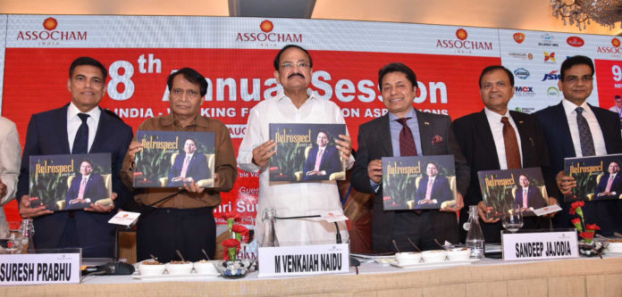 The Vice President, Shri M. Venkaiah Naidu releasing the souvenir at the 98th Annual Session of the Associated Chambers of Commerce and Industry of India (ASSOCHAM), in New Delhi on October 16, 2018. The Union Minister for Commerce & Industry and Civil Aviation, Shri Suresh Prabhakar Prabhu and other dignitaries are also seen.