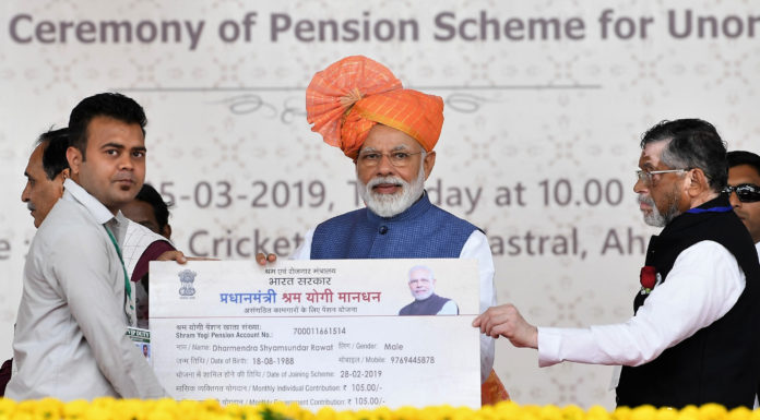 The Prime Minister, Shri Narendra Modi distributing the PM-SYM Pension Cards to select beneficiaries, at a function, in Vastral, Gujarat on March 05, 2019. The Minister of State for Labour and Employment (I/C), Shri Santosh Kumar Gangwar is also seen.