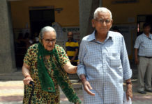 An old couple voters arrive at a polling booth, during the 6th Phase of General Elections-2019, at Rohini, in New Delhi on May 12, 2019.