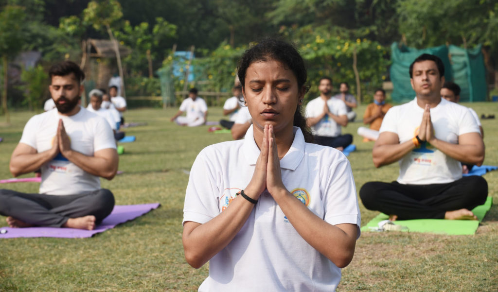 People perform Yoga, on the occasion of the 7th International Day of Yoga 2021, at Wazirabad in Delhi on June 21, 2021.